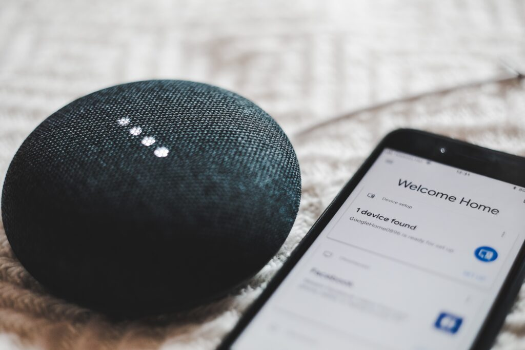 """Active gray Google Home Smart Speaker pairs with a smartphone that reads """"Welcome home"""