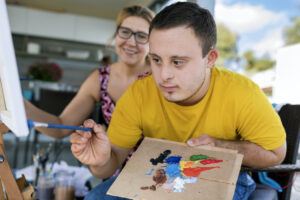 Teen with Down syndrome uses a palette to paint on canvas. His art therapist smiles in the background.