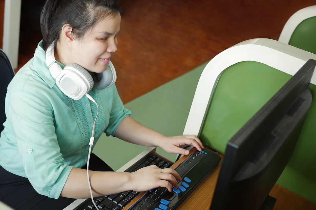 A photo of a blind woman with headphone uses computer with a braille terminal, a technology device for persons with visual disabilities.