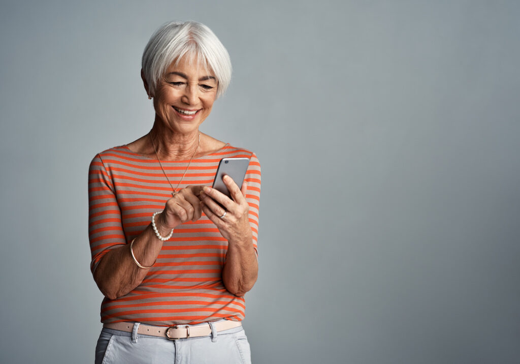 Women delights in the content of her search results on her mobile device.