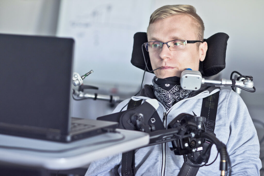 A photo of a disabled user with a lot of personal assistive technology uses a laptop computer.