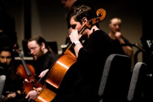 A photo of a cellist with smartwatch and the orchestra in the background.