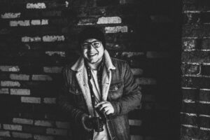 A photo of a smiling photographer with a toque and glasses holds his camera in front of a brick wall.